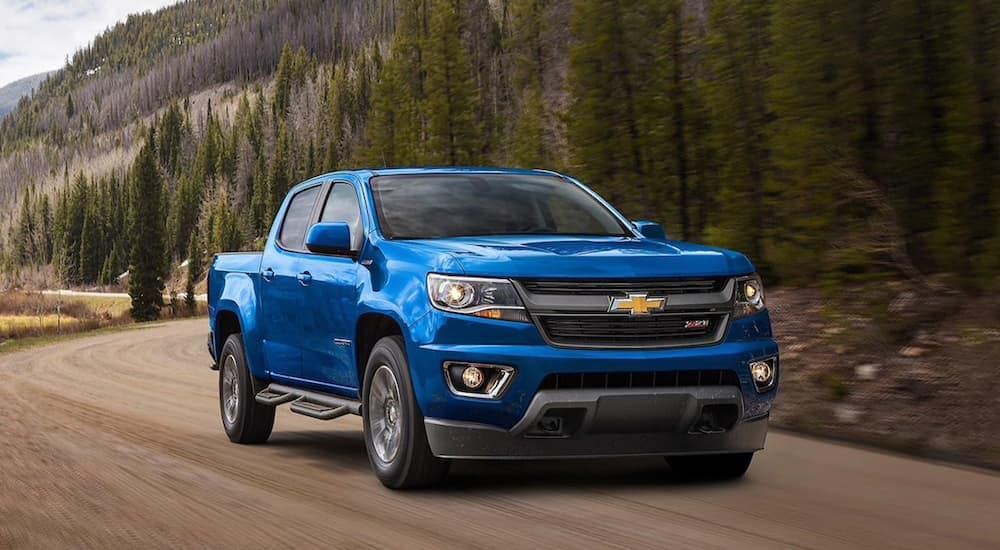 A blue 2020 Chevy Colorado, which is popular among trucks for sale in Albany, NY, is driving on a dirt road.