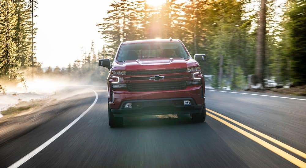 A red 2020 Chevy Silverado 1500, which is popular among trucks for sale in ALbany, NY, is driving on a misty road.