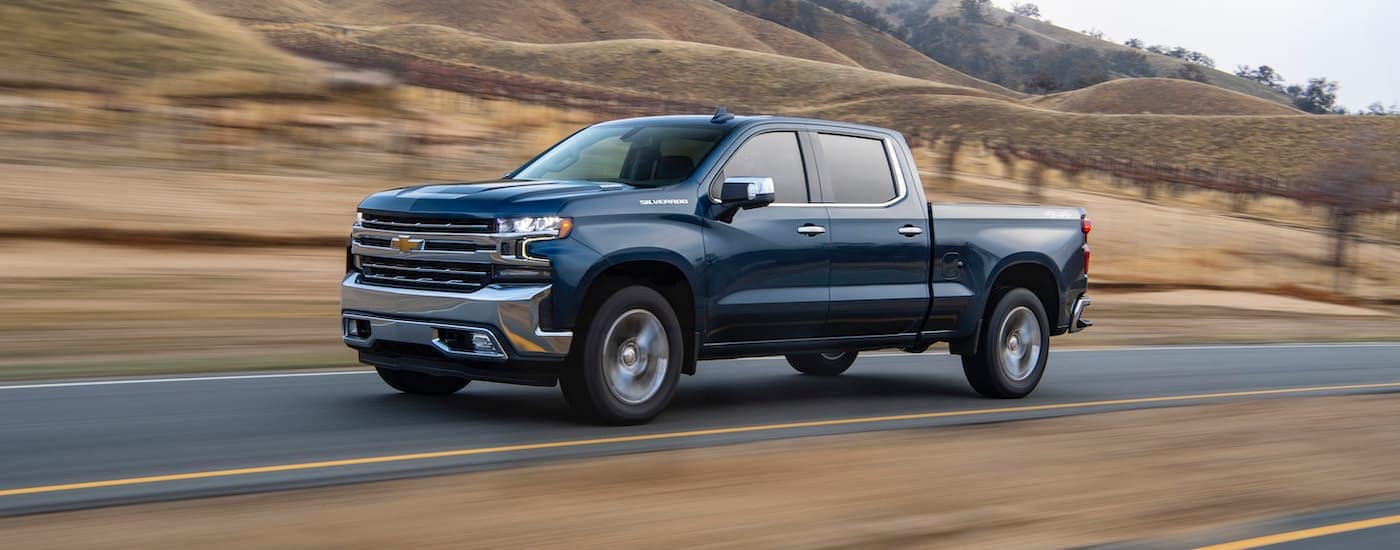 A blue 2020 Chevy Silverado 1500 is driving past hills near Albany, NY.