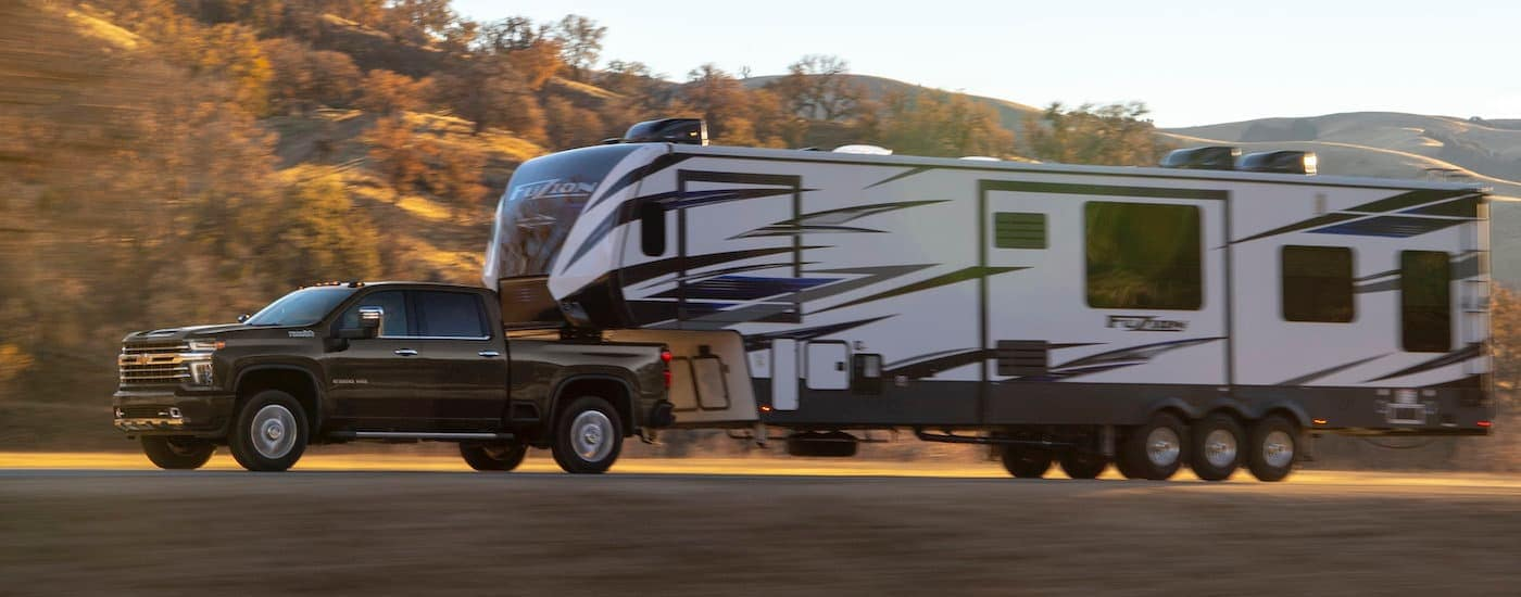 A dark grey 2020 Chevy Silverado 2500HD is towing a large camper on a fall day.