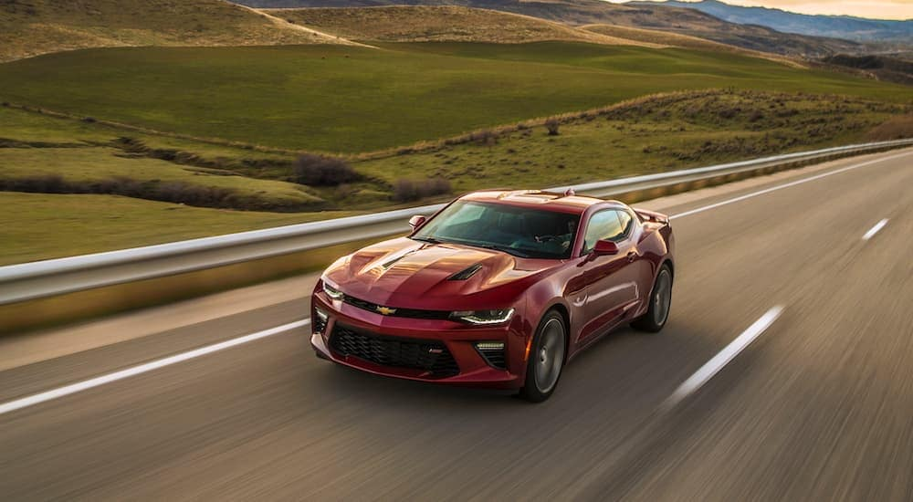 A red 2017 Chevy Camaro, which is popular among used cars in Albany, NY, is driving past rolling hills.