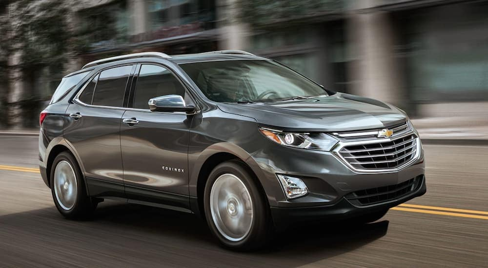 A dark grey 2019 Chevy Equinox is driving on a city street.