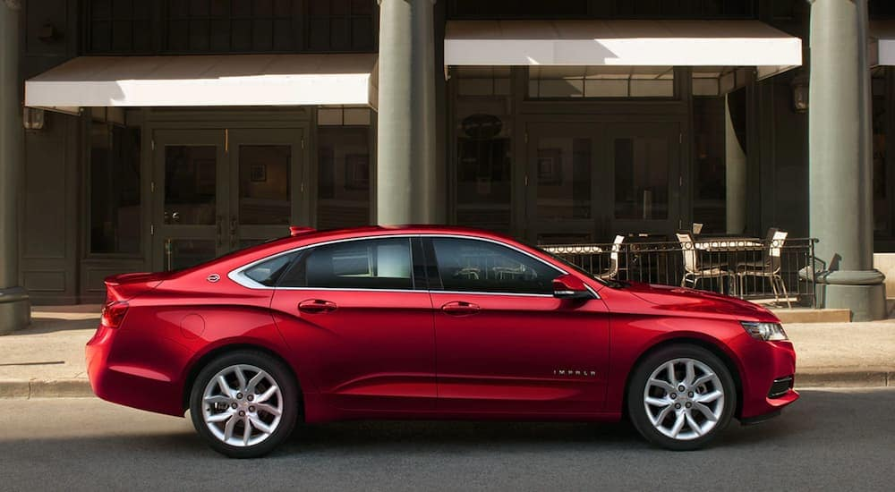 A red 2019 Chevy Impala is shown from the side in front of a city building.