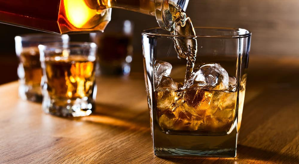 Whiskey is being poured into a glass.