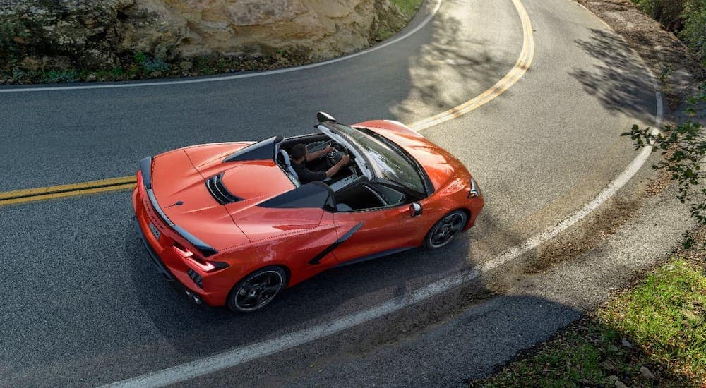 An orange 2020 Chevy Corvette Stingray Convertible is shown from above driving on a mountain road.