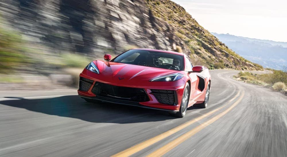 A red 2020 Chevy Corvette Stingray driving on a highway away after leaving a Chevy Dealership Clifton Park, NY.