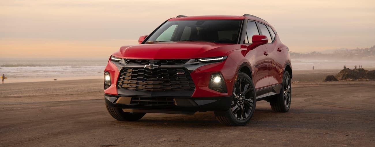 A red 2020 Chevy Blazer, which wins when comparing the 2020 Chevy Blazer vs 2020 Ford Edge, is parked on the sand at a beach.