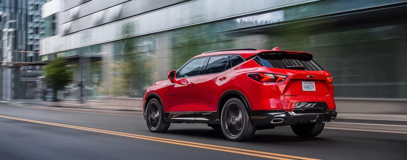 A red 2020 Chevy Blazer is driving on a city street near Albany, NY.
