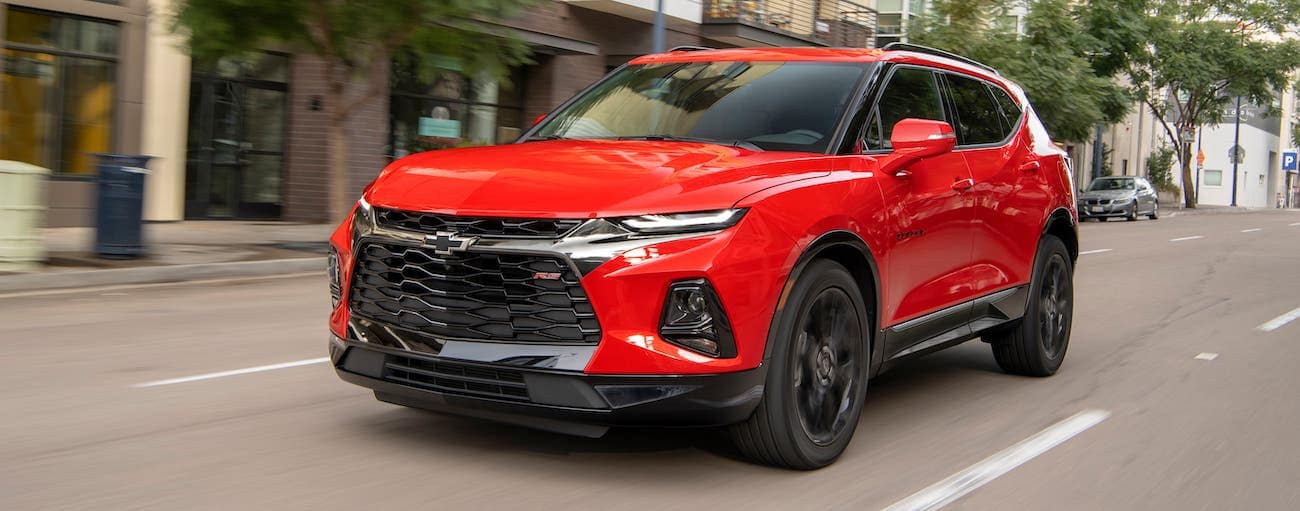 A red 2020 Chevy Blazer RS is driving on a city street outside of Albany, NY.