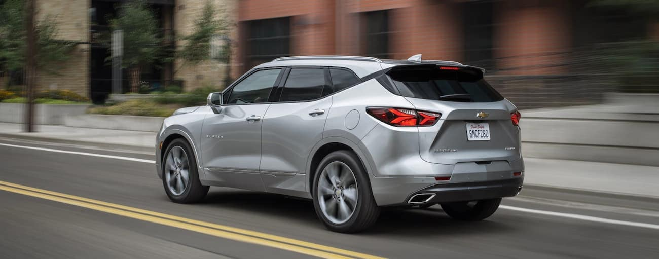A silver 2020 Chevy Blazer is driving on a city street.