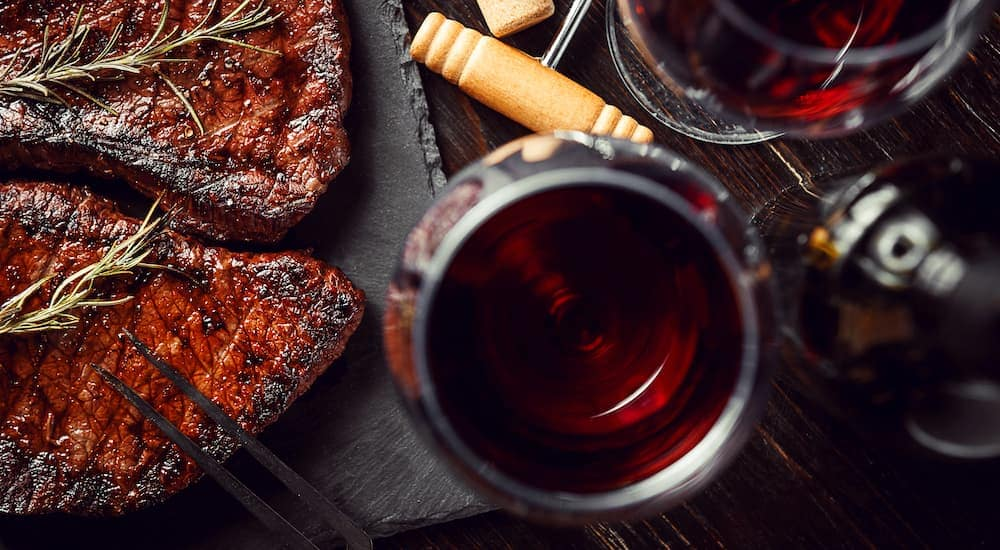 Steak and glasses of red wine are shown from above.