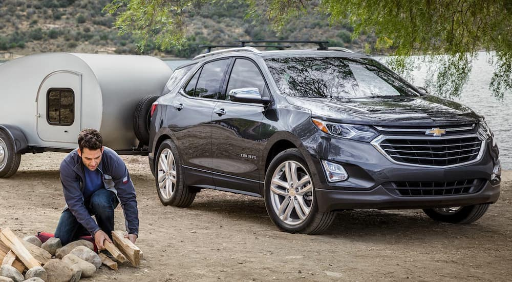 A man is starting a campfire next to his grey 2020 Chevy Equinox that is hooked up to a very small camper.