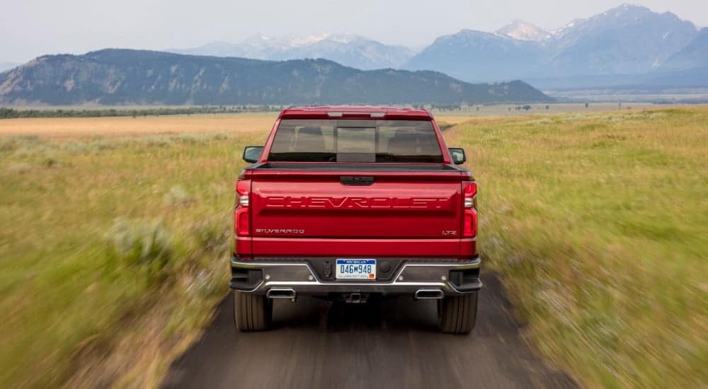 The rear of a red 2020 Chevy Silverado LTZ is shown on a dirt road.