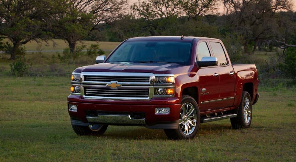 A red 2014 Chevy Silverado 1500 is parked in a field in front of trees at sunset.