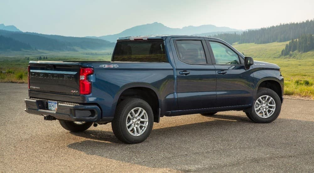 A blue 2020 Chevy Silverado 1500 is shown from the rear with mountains in the distance.