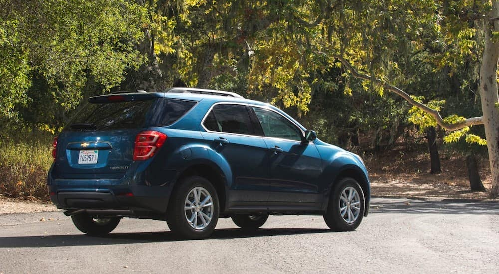 A blue 2016 Chevy Equinox is parked in front of trees.