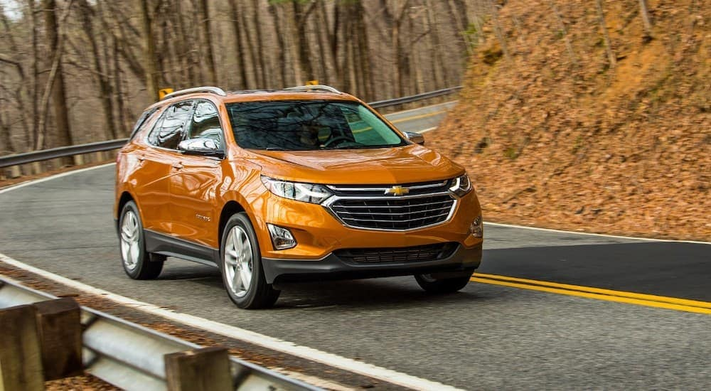 An orange 2019 Chevy Equinox is driving on a winding road in the fall near Albany, NY.