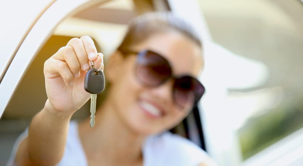 A woman is out of focus while she holds a car key in front of her.