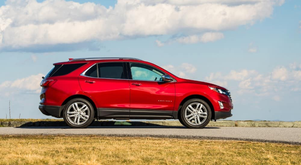 Red 2020 Chevrolet Equinox driving down a paved road next to green grass in front of a blue sky