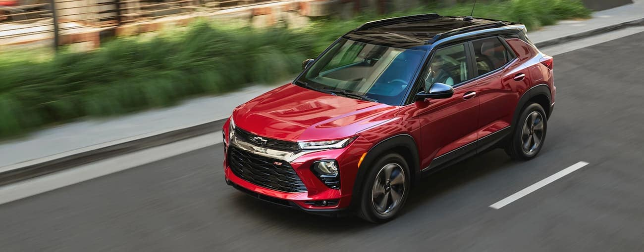 A red 2021 Chevy Trailblazer RS is driving on a highway past bushes near Albany, NY.