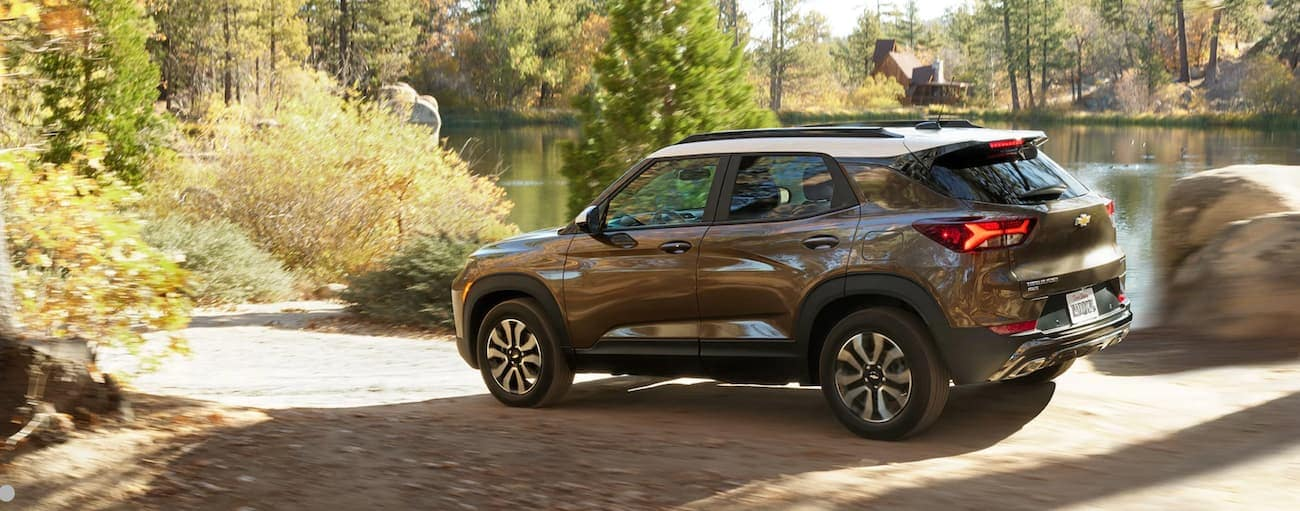 A brown and white 2021 Chevy Trailblazer is driving around a lake in Albany, NY.