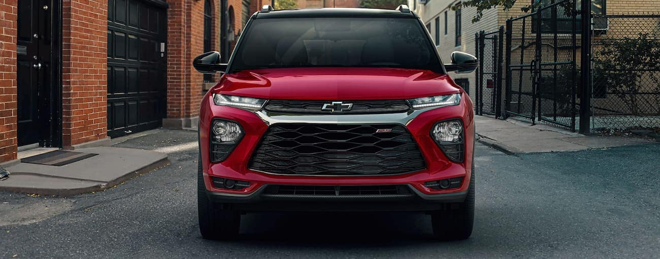 A red 2021 Chevy Trailblazer is parked in a city alley way.
