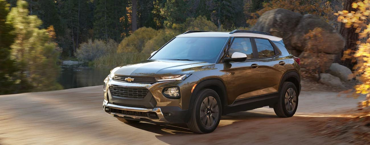 A brown and white 2021 Chevy Trailblazer is driving on a dirt road near Albany, NY.