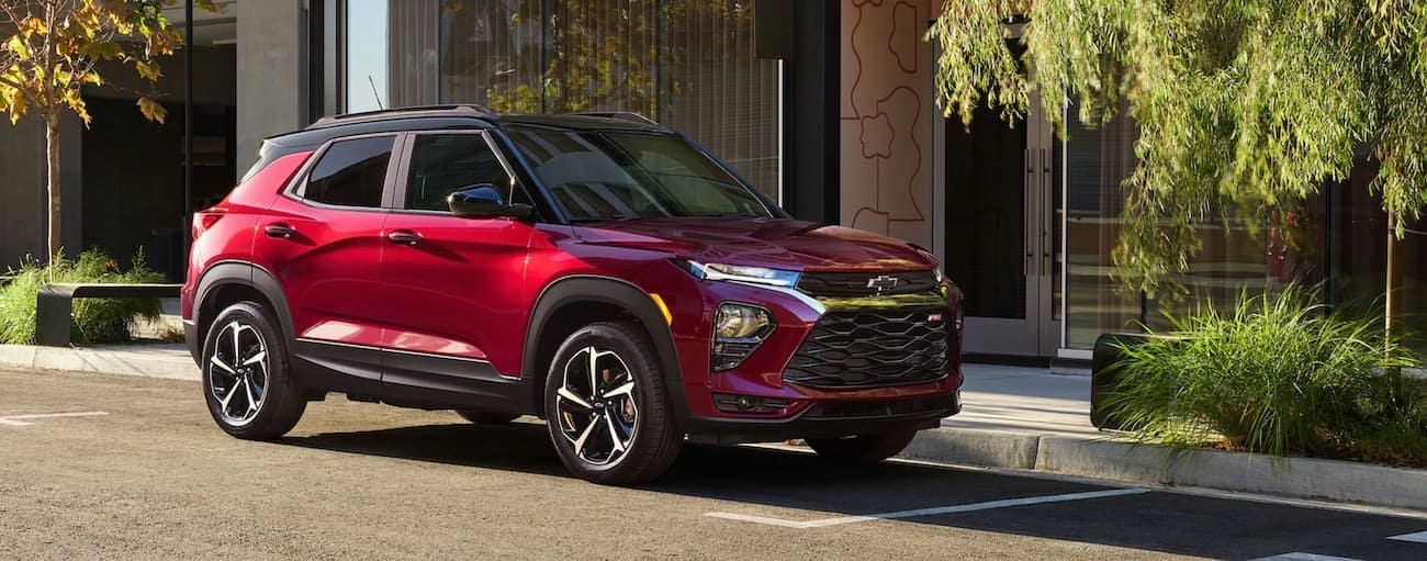 A red 2021 Chevy Trailblazer RS, which wins when comparing the 2021 Chevy Trailblazer vs 2020 Nissan Kicks, is parked in front of city buildings.