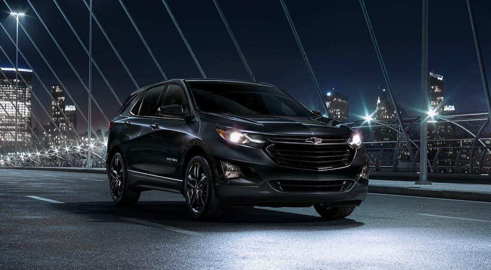 A black 2020 Chevy Equinox is driving away from a city at night.