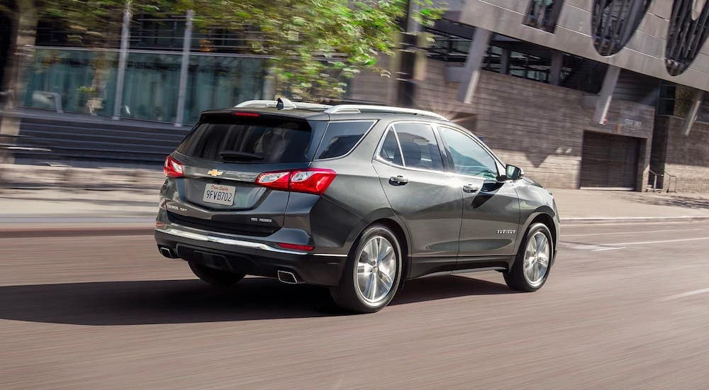 A gray 2020 Chevy Equinox is driving on a city street after leaving a Chevy dealer in Albany, NY.