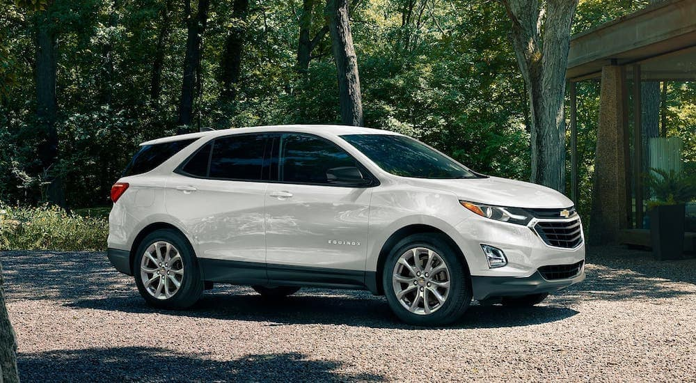 A white 2020 Chevy Equinox is parked in front of a house in the woods.