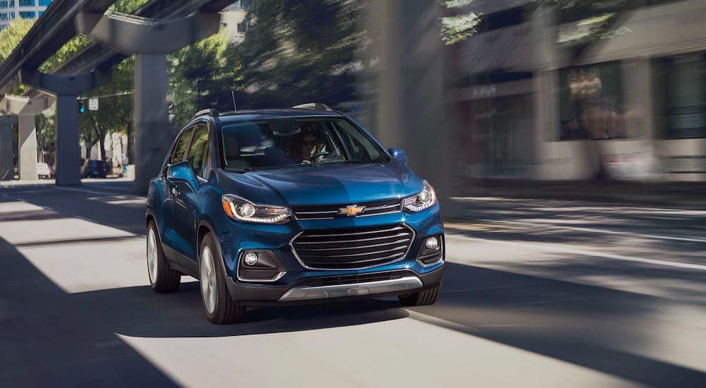 A blue 2020 Chevy Trax is racing away with a win between 2020 Chevy Trax vs 2020 Chevy Equinox.