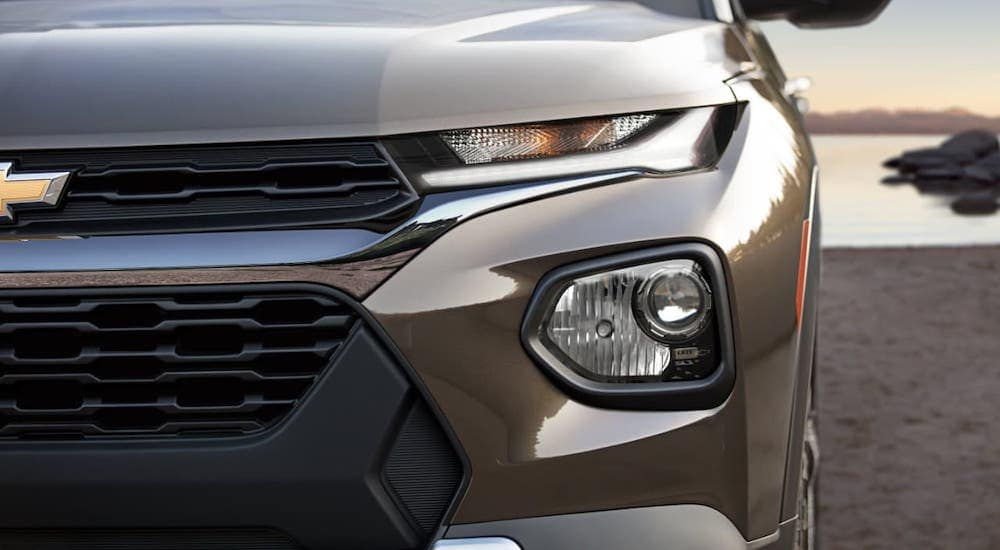 A closeup of a new Chevy vehicle, a brown 2021 Chevy Trailblazer, is shown from the front.