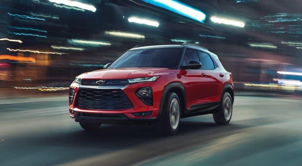 A red 2020 Chevy Trailblazer RS is driving through Albany, NY, at night.
