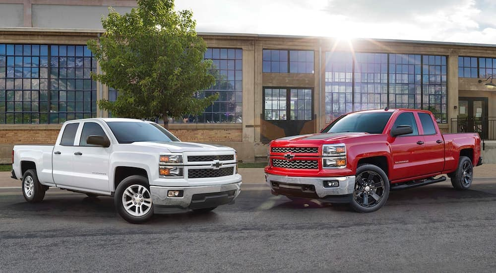A white and a red 2015 Chevy Silverado are parked at a used car dealership building near Albany, NY.