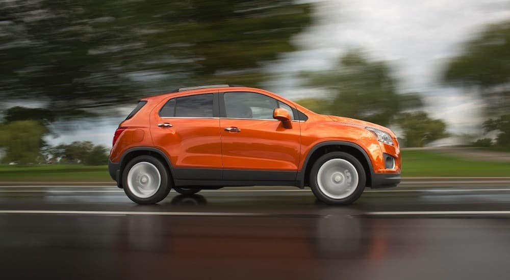 An orange 2015 Chevy Trax is driving in the rain.