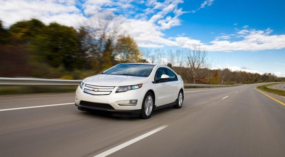 A white 2015 Chevy Volt is driving on a highway near Albany, NY, after leaving a used car dealership.