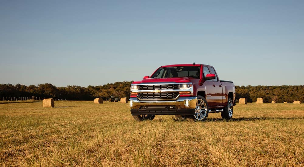 A red 2016 Chevy Silverado is parked in a hay field.