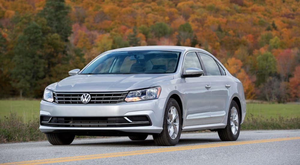 A silver 2017 Volkswagen Passat is driving past fall foliage.