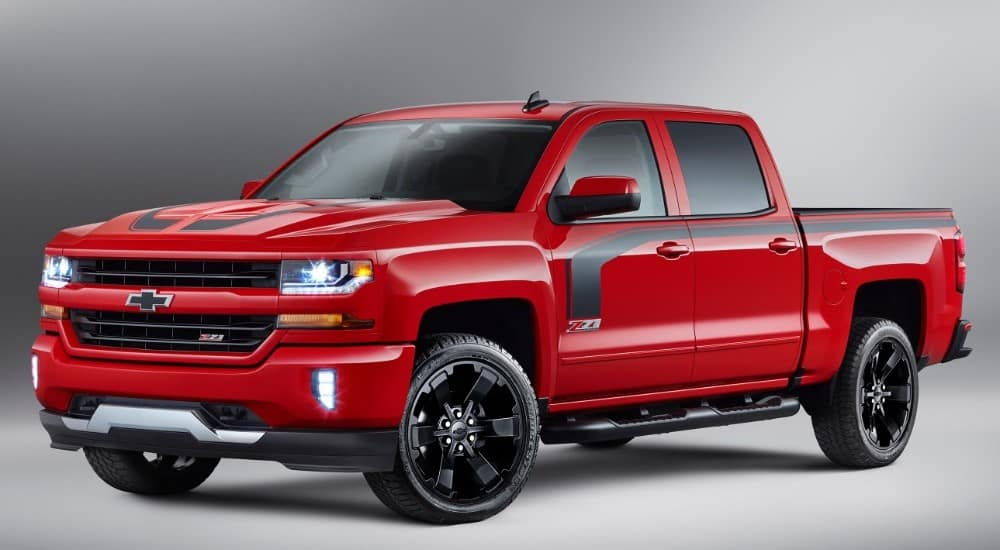 Red and black Chevy Silverado truck against a grey background