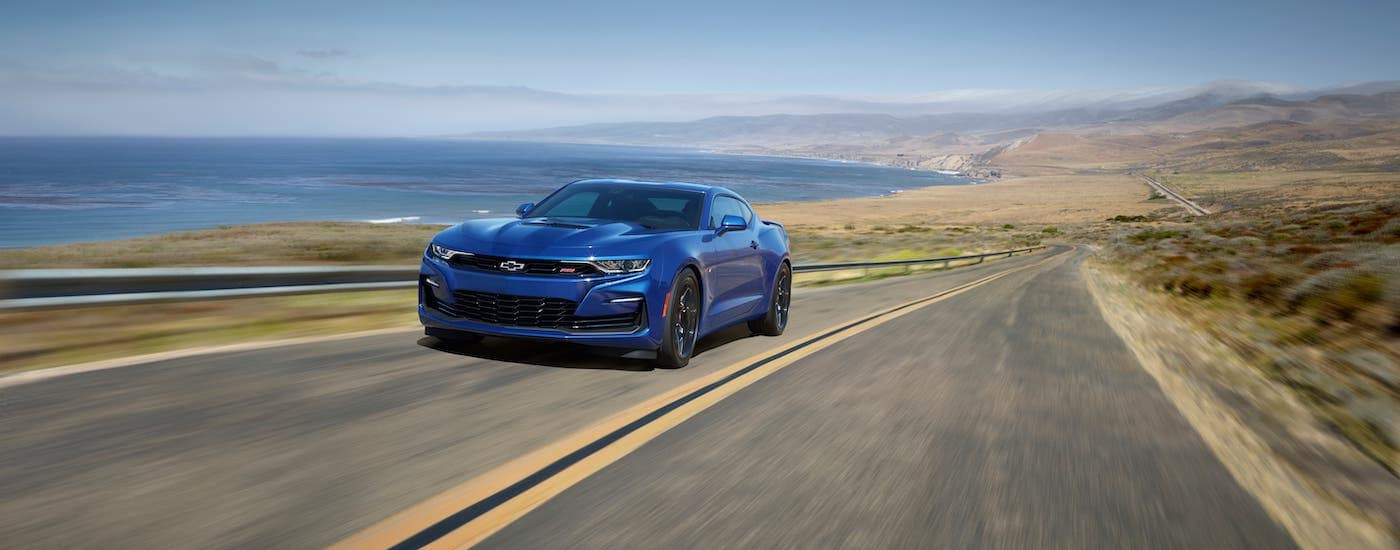 A blue 2020 Chevy Camaro SS is driving along a coastal highway.