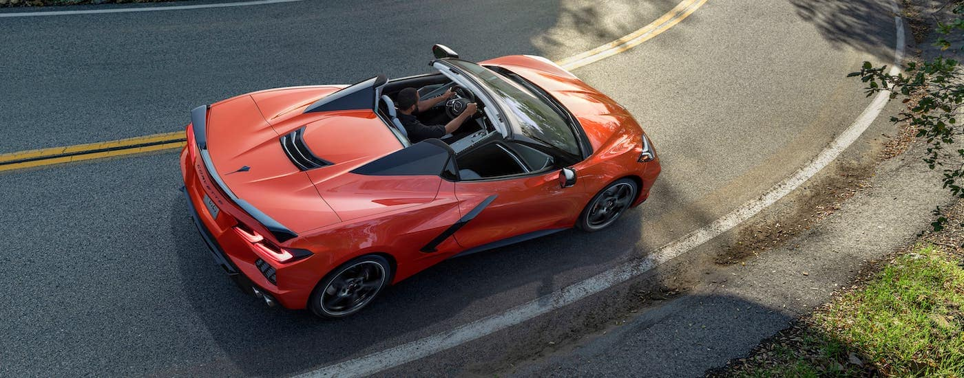 An orange 2020 Chevy Corvette Stingray Convertible is shown from above driving on a highway.