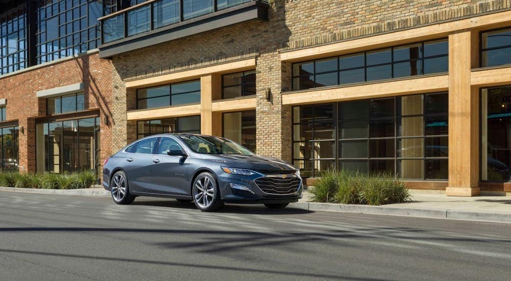 One of the many Chevy cars available at your local Albany dealer, a gray 2020 Chevy Malibu is shown driving on a street.