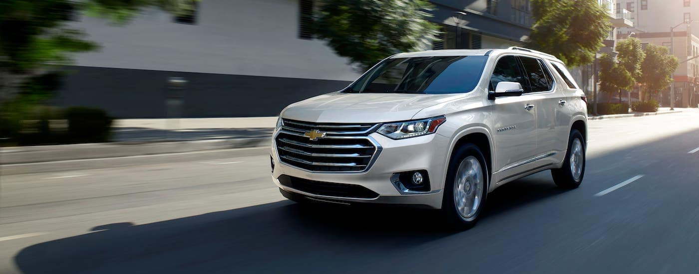 A white 2020 Chevy Traverse is driving on a street near Albany.