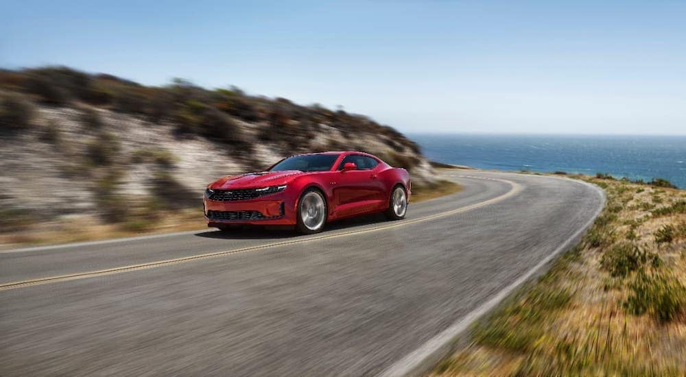 A red 2020 Chevy Camaro LT is driving along an ocean-side highway.