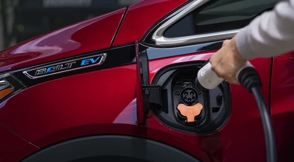 A closeup is shown of a red 2020 Chevy Bolt being charged.
