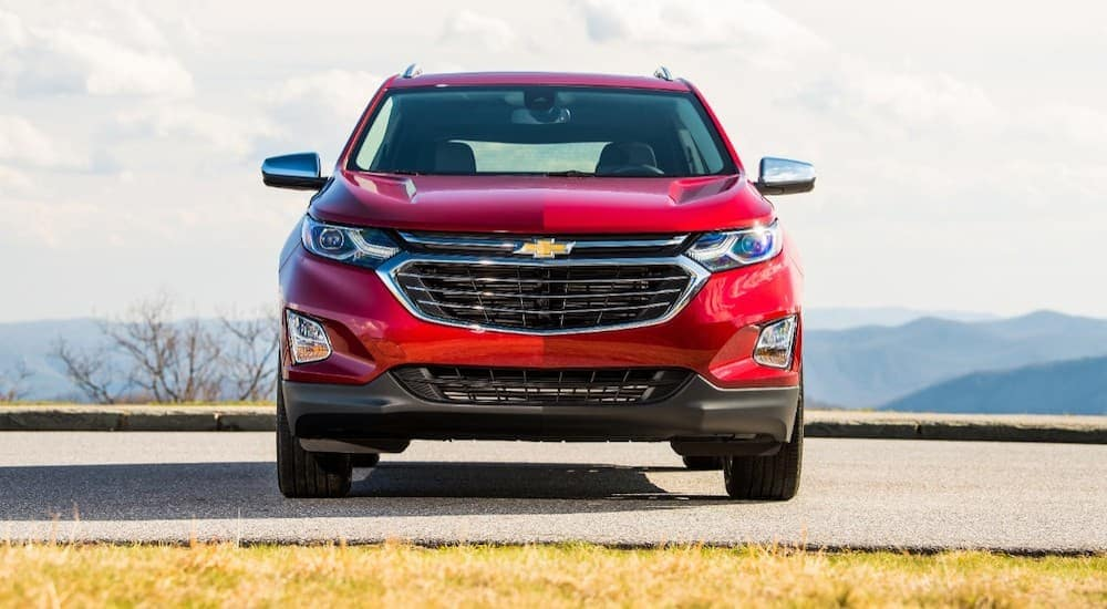 A red 2018 Chevy Equinox is shown from the front with hills in the distance.