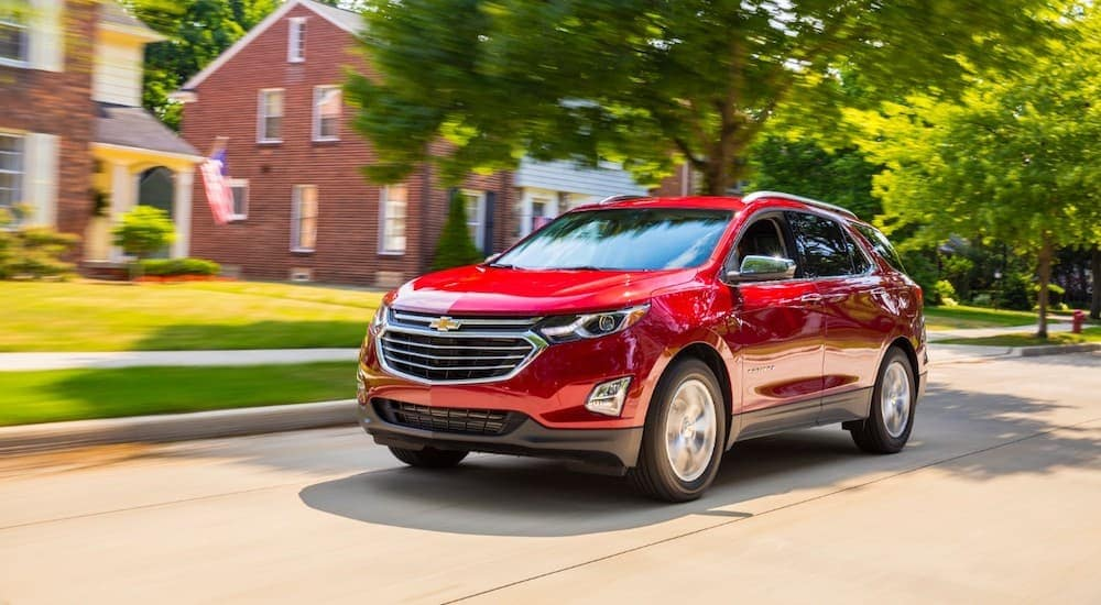 A red 2018 Chevy Equinox is driving through a neighborhood with brick homes.