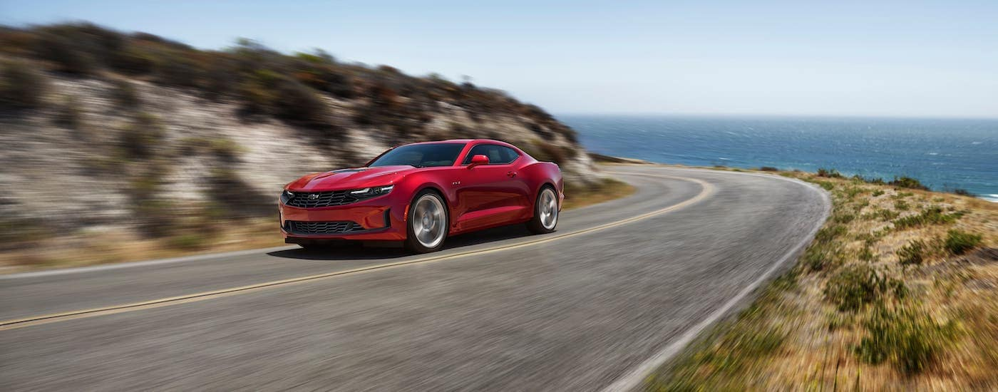 A red 2020 Chevy Camaro LT1 is driving on a highway near the ocean.