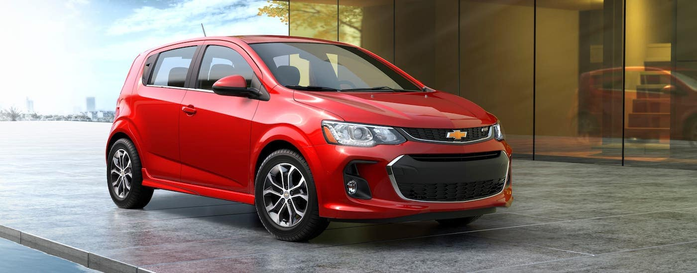 A red 2020 Chevy Sonic is parked in front of a modern building.